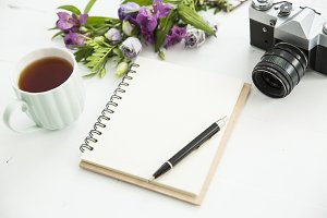 Desk with tea, notebook and flowers