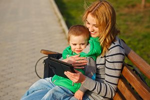 Mother and son play with a tablet pc