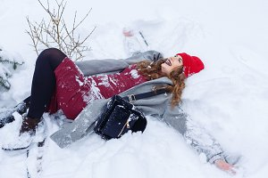 Hipster Girl making angel in snow