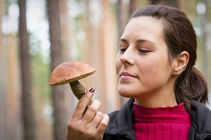 Woman with mushroom in forest