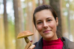 Woman with edible mushroom in the forest