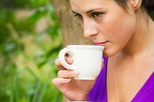Woman drinks coffee outdoors