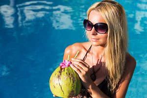 Young pretty blonde woman in swimming pool with coconut cocktail