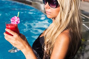 Young pretty blonde woman swimming pool with water melon cocktail