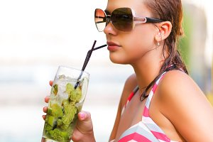 Woman drinks near swimming pool
