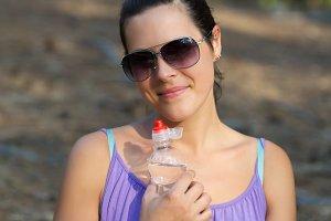 Woman drinks water plastic bottle