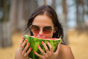 Woman eats water-melon on beach