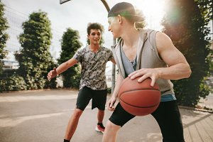 Two young friends playing basketball