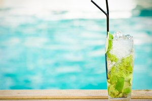 Mohito mojito drink with ice mint and lime near swimming pool