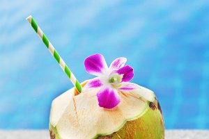 Fresh coconut drink with orchid flower and swimming pool