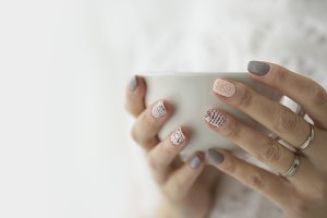 woman's hands holding a white cup
