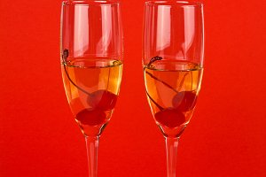 Two champagne glasses with cherry