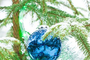 Christmas baubles on tree in snow