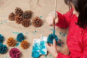 Child painting pinecones