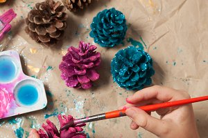 Child painting pine cones