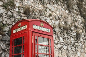 Red telephone cabin and stone wall
