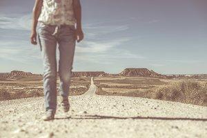 Woman walking on dirt road