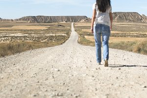 Woman walking on dirt road