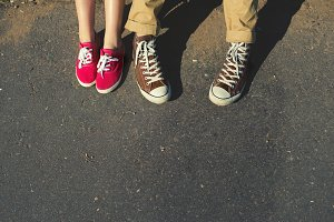 legs of a young couple in sneakers