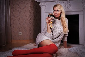 Blond woman near fireplace with champagne glass
