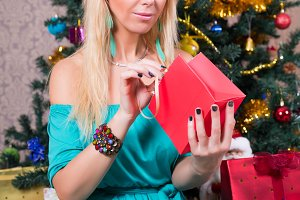 Pretty woman with present bag near Christmas tree