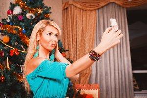 Pretty woman taking selfie photo on mobile phone Christmas tree