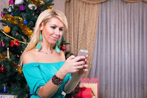 Pretty woman typing sms on mobile phone near Christmas tree