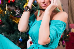 Pretty woman speaks on mobile phone near Christmas tree
