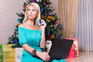 Pretty woman with laptop credit card buying presents Christmas tree