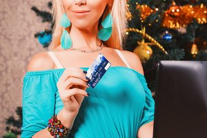 Pretty woman with laptop and credit card buying presents near Christmas tree
