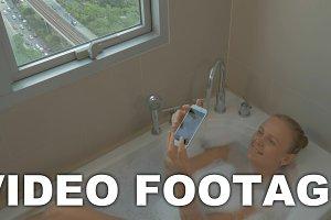 Woman in bath taking selfie