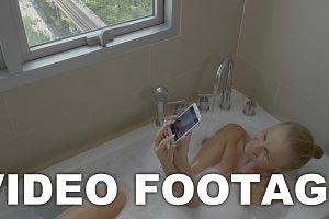 Woman having bath and making selfie