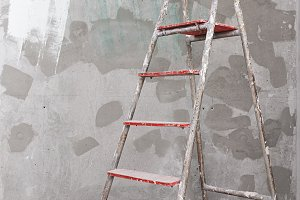 Old painted stucco ladder on concrete wall background