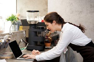 Cute Caucasian busy working with laptop on coffee shop counter