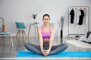Young Caucasian woman stretching and doing yoga at home