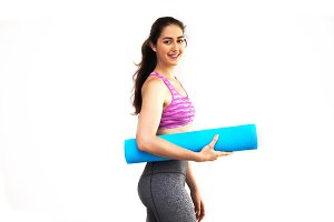 Young beautiful Caucasian woman in sportswear carrying yoga mat in white isolated background