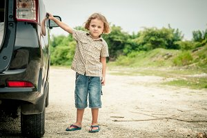 Happy little boy standing near car