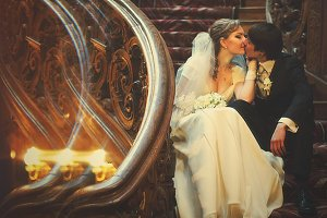 Newlyweds sits on the old stairs