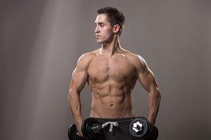 Bodybuilder two dumbbells studio