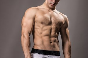 Bodybuilder young man posing studio