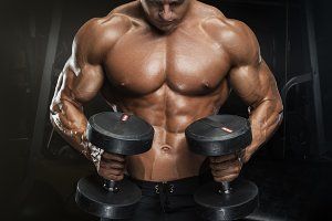 Athletic guy workout with dumbbells