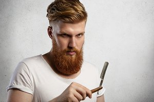 Good-looking professional barber with thick red beard and mustache, holding straight razor. Young Caucasian hairdresser wearing white t-shirt demonstrating sharp blade of his barbershop accessory