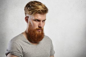 Portrait of courageous model with long fuzzy beard and trendy haircut posing indoors. Studio shot of Caucasian young hipster man wearing gray T-shirt with rolled sleeves looking gloomily ahead of him