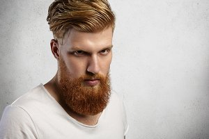 Close up portrait of serious attractive young European man with long fuzzy beard, looking at camera woth sullen face expression, posing against gray wall background with copy space for your content