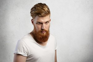 Headshot of self-assured bearded hipster with stylish haircut and muscular build wearing t-shirt with rolled sleeves looking with severe expression, angry with something. Isolated shot, horizontal