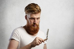 Fashionable redhead barber with stylish haircut and fuzzy beard holding cut-throat razor in his hands, looking at camera with serious face expression. Caucasian hairdresser showing his straight razor