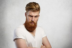 Studio shot of attractive bearded young Caucasian male dressed in white t-shirt standing on blank wall background with copy space for your text or advertising content, looking serious and confident