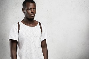 Style, design and fashion. Studio shot of serious good-looking African student wearing leather backpack and white stylish T-shirt standing against blank wall background with copy space for your content,