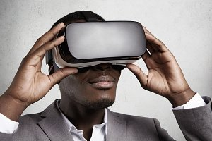 Technology and entertainment. Successful dark-skinned office worker in elegant gray suit experiencing virtual reality using VR headset glasses. Black man wearing oculus or goggles playing video games