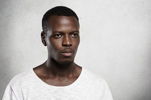 Isolated shot of stylish fashionable African model dressed in white T-shirt, posing in studio with serious expression. Tired dark-skinned student spending free time indoors after lectures at college